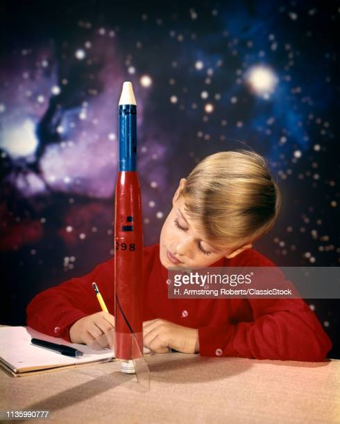 1960s BOY WITH MODEL ROCKET WRITING ON NOTE PAD WITH PENCIL STAR GALAXY IN BACKGROUND