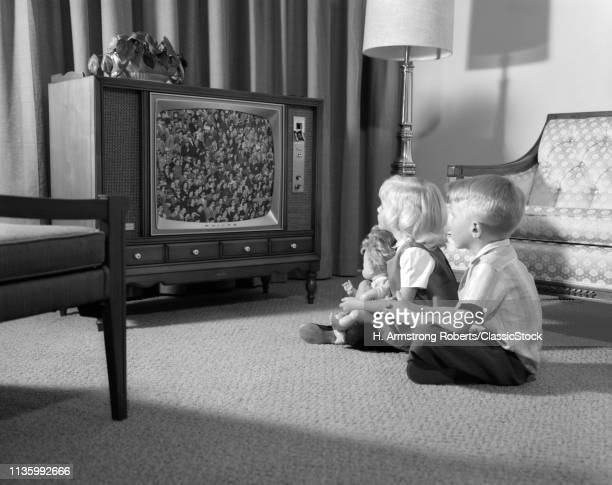 1960s BROTHER & SISTER SITTING ON LIVING ROOM FLOOR WATCHING TV