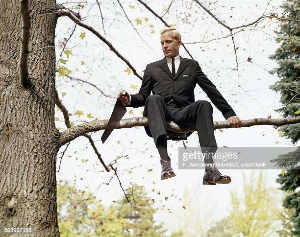 1960s BUSINESS MAN IN TREE...
