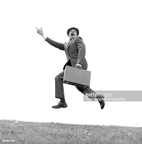 1960s BUSINESSMAN CARRYING A BRIEFCASE RUNNING YELLING AND JUMPING IN THE AIR OUTDOOR POINTING FINGER FORWARD