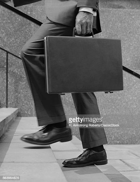 1960s BUSINESSMAN LEGS WALKING UP STAIRS HAND HOLDING BRIEFCASE