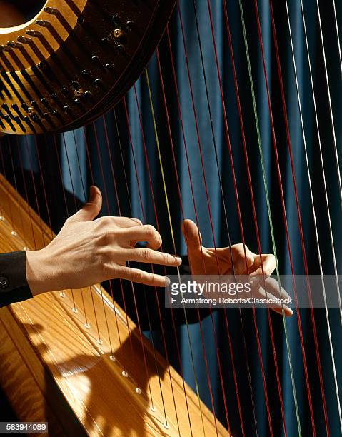 1960s CLOSE UP OF FEMALE HANDS PLUCKING STRINGS PLAYING HARP