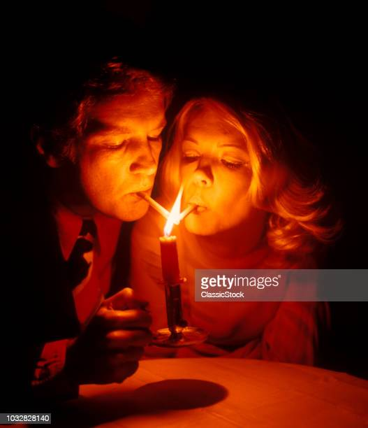 1960s COUPLE MAN WOMAN ROMANTIC LIGHTING CANDLELIGHT LIGHTING CIGARETTES