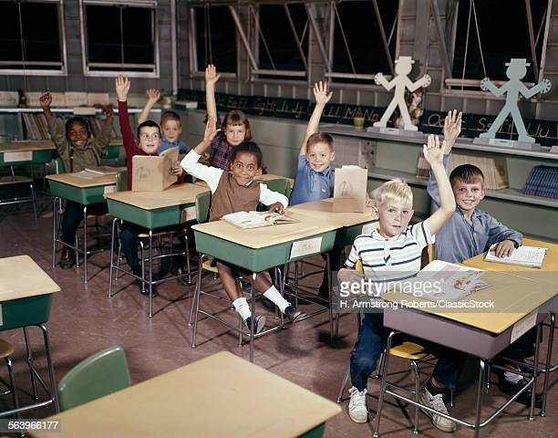 1960s diverse elementary school children in classroom with hands raised to answer question.