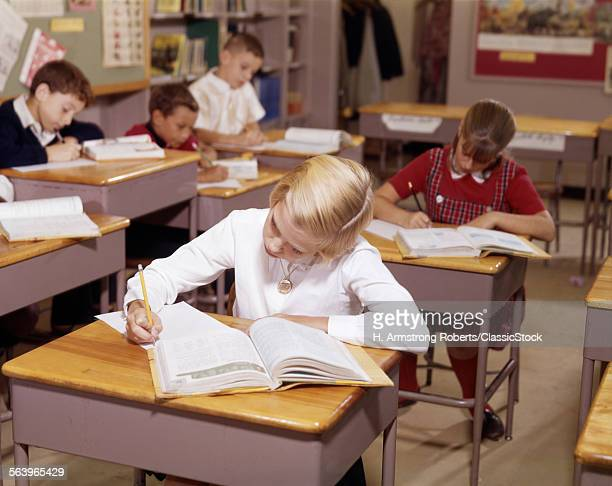 1960s ELEMENTARY SCHOOL CHILDREN IN CLASSROM AT DESKS WORKING WITH BOOKS AND PAPERS BOY GIRL