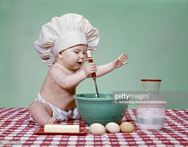 1960s ENERGETIC BABY GIRL IN CHEF HAT USING SPOON AND MIXING BOWL STUDIO EGGS BUTTER MILK