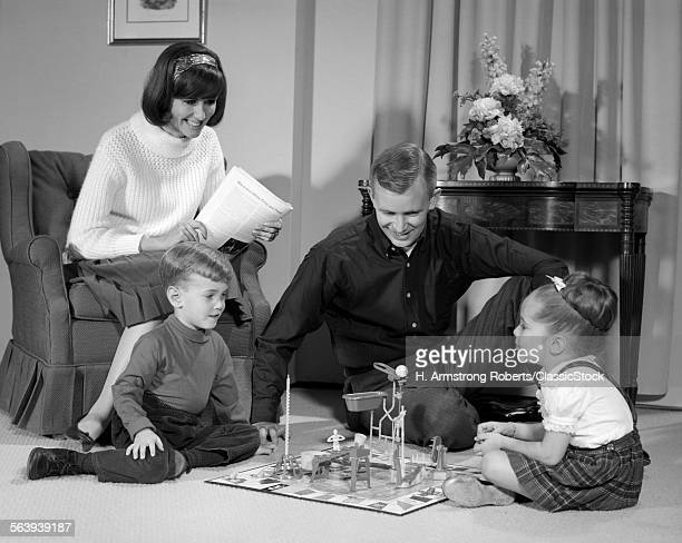 1960s FAMILY CHILDREN PLAYING GAME IN LIVING ROOM MOUSETRAP