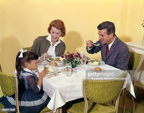 1960s FAMILY ENJOYING DINNER TOGETHER AT TABLE INDOOR MAN WOMAN GIRL