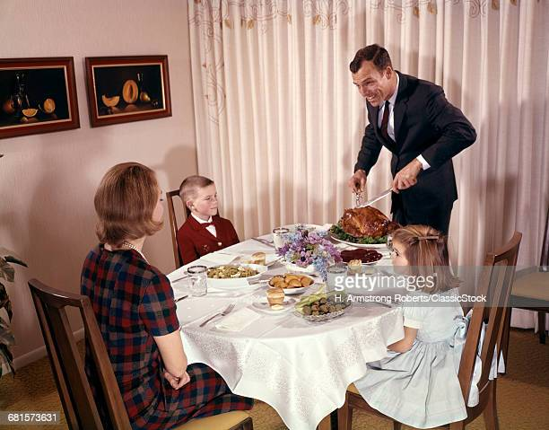 1960s FAMILY HOLIDAY DINNER FATHER CARVING TURKEY MOTHER BOY AND GIRL SEATED AT DINING ROOM TABLE