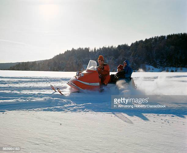 1960s FAMILY MOTHER FATHER DAUGHTER RIDING ON SNOWMOBILE WINTER SNOW RECREATION