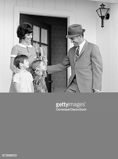 1960s FAMILY STANDING ON FRONT STEPS FATHER CARRYING BRIEFCASE SAYING GOODBYE GOING TO WORK
