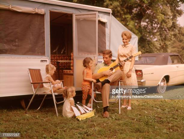 1960s FAMILY VACATION RV POP UP CAMPER MOTHER THREE CHILDREN ALL GIRLS FATHER SITTING PLAYING GUITAR
