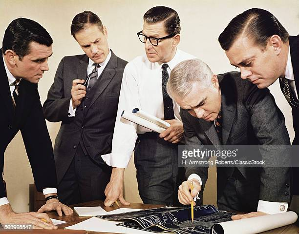 1960s FIVE MEN IN BUSINESS PLANNING MEETING REVIEWING BLUEPRINTS AND DOCUMENTS