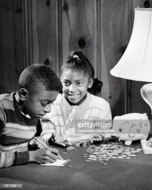 1960s Frugal Smiling AfricanAmerican Boy Girl Brother Sister Counting Money From Their Piggy Bank
