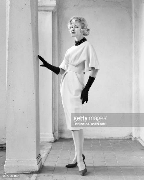 1960s FULL LENGTH PORTRAIT ELEGANT BLONDE WOMAN WEARING DRESS WITH FULL DRAPED SLEEVES LONG GLOVES POSING BY COLUMN OUTDOORS