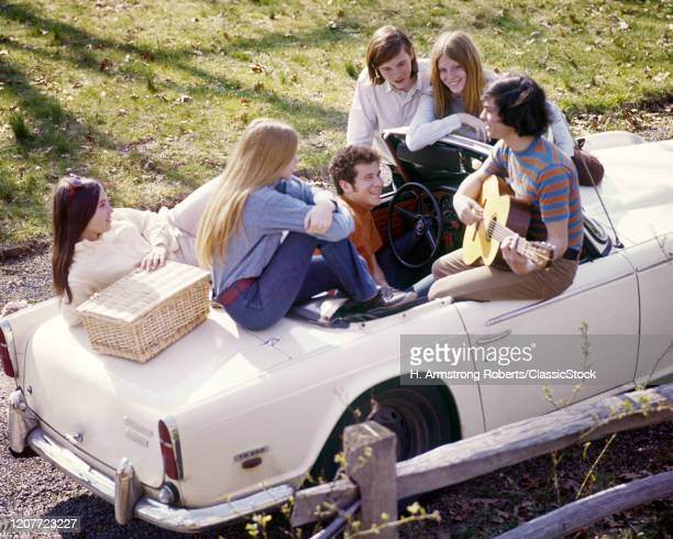 1960s group six stylish teens on white triumph convertible with picnic basket listening to kid playing the guitar.