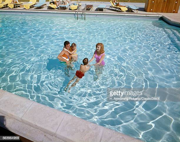1960s HAPPY FAMILY FATHER MOTHER SON DAUGHTER SWIMMING TOGETHER IN MOTEL SWIMMING POOL