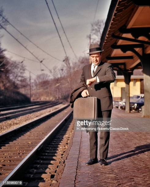 1960s HARRIED BUSINESS MAN CHECKING TIME WRIST WATCH WAITING FOR COMMUTER TRAIN AT SUBURBAN STATION