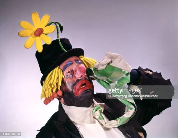 1960s Hobo Style Clown Wearing Top Hat With Big Daisy Performing Crying Wiping His Eyes With Necktie