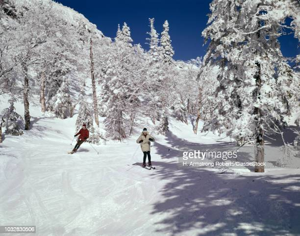 1960s MAN AND WOMAN SKIING ON SNOWY WINTER SLOPES