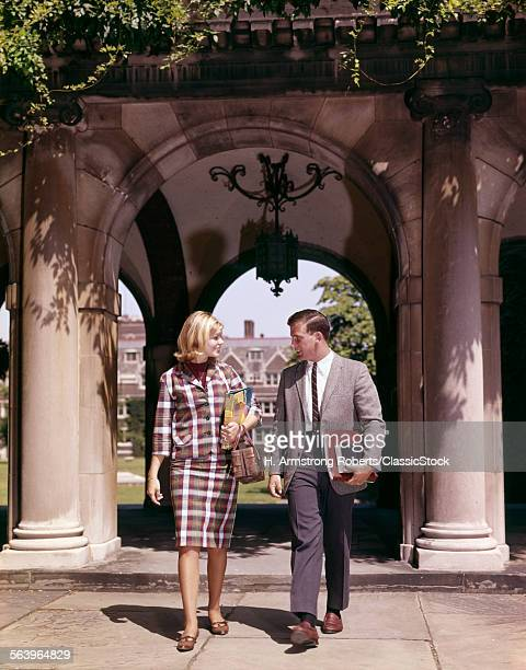 1960s MAN AND WOMAN STUDENTS WITH BOOKS AT ARCH LEADING TO CAMPUS QUADRANGLE