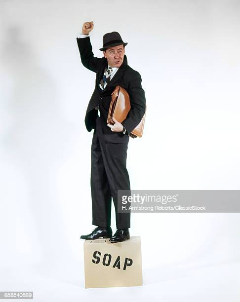 1960s MAN IN BUSINESS SUIT HOLDING BRIEF CASE STANDING ON SOAPBOX LOOKING AT CAMERA AND SHAKING FIST AS HE SPEAKS