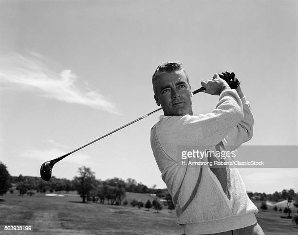 1960s MAN PLAYING GOLF TEEING-OFF GOLF BALL FROM TEE WITH DRIVER OUTDOOR