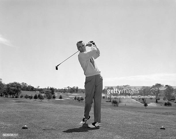 1960s MAN PLAYING GOLF TEEING OFF FROM TEE USING DRIVER