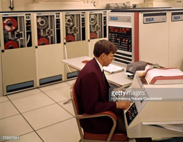 1960s MAN PROGRAMMER ENTERING DATA ON SYSTEM CONSOLE KEYBOARD IN COMPUTER ROOM WITH MAINFRAME TAPE STORAGE DRIVE MACHINES