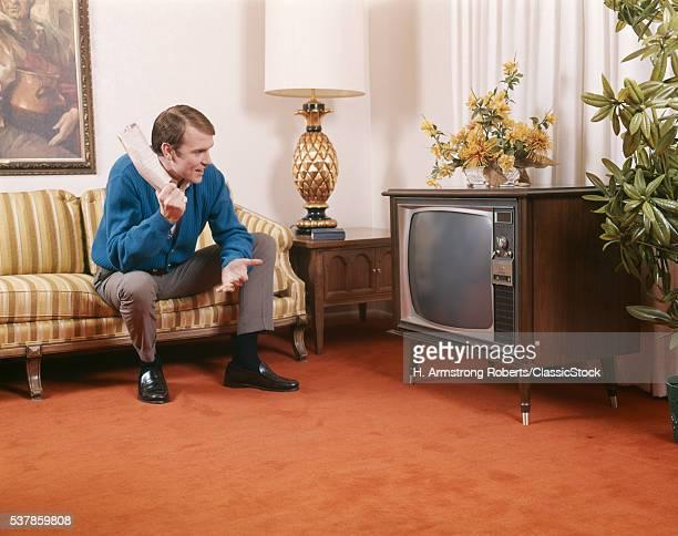 1960s MAN SITTING ON SOFA...