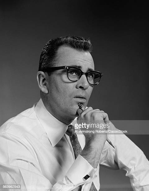 1960s MAN THINKING HAND PENCIL ON CHIN WEARING EYEGLASSES SERIOUS EXPRESSION