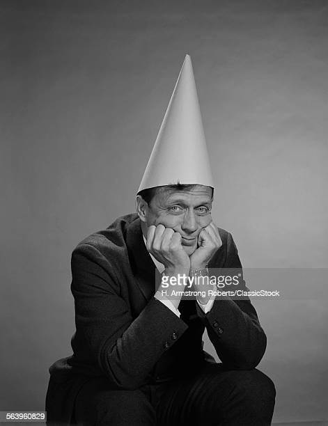 1960s MAN WEARING DUNCE CAP