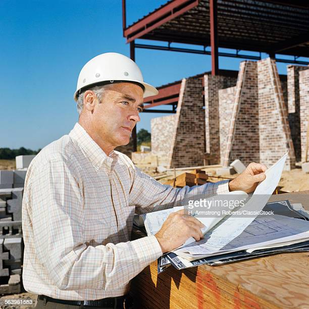 1960s MAN WEARING CONSTRUCTION HARD HAT BLUEPRINTS PLANS ENGINEER ARCHITECT
