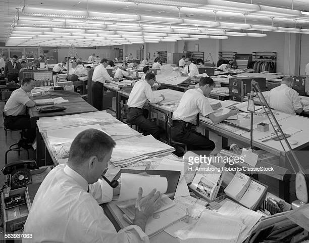 1960s MEN SITTING AT...