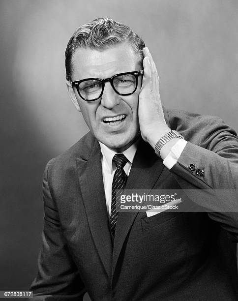 1960s MIDDLE AGED MAN WITH ANGRY PAINFUL FACIAL EXPRESSING HOLDING HAND TO SIDE OF HEAD
