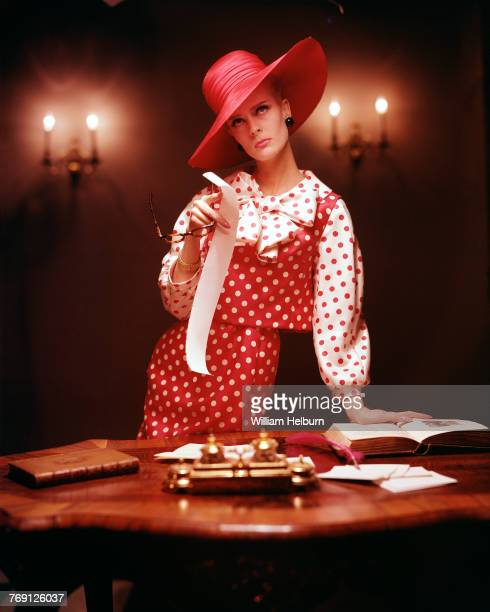 Model Angela Howard Helburn in red hat and red and white polka dots poses in front of a table for McCall's magazine