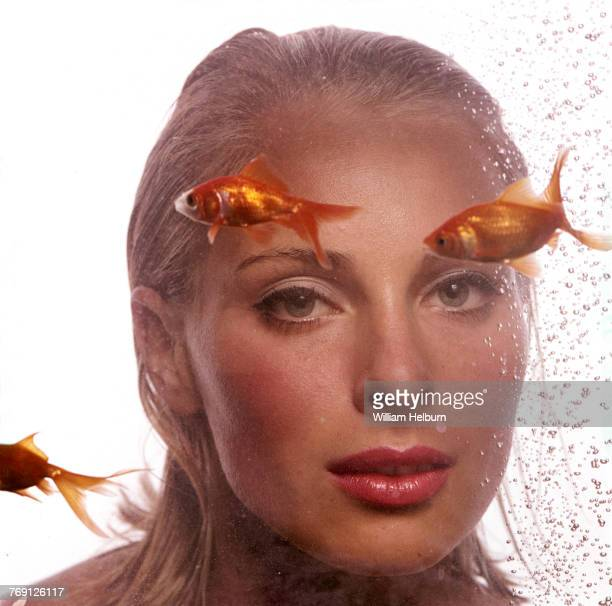 Model/actress Camilla Sparv posed in front of white background/behind aquarium showing three goldfish and air bubbles