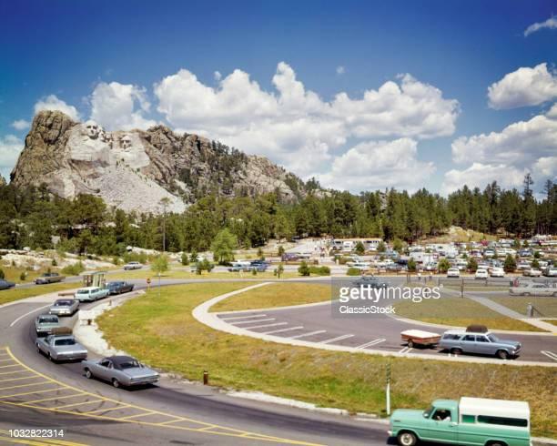 1960s MOUNT RUSHMORE NATIONAL MEMORIAL PARKING LOT CARS FOREGROUND SCULPTURE IN BACKGROUND BLACK HILLS KEYSTONE SOUTH DAKOTA USA