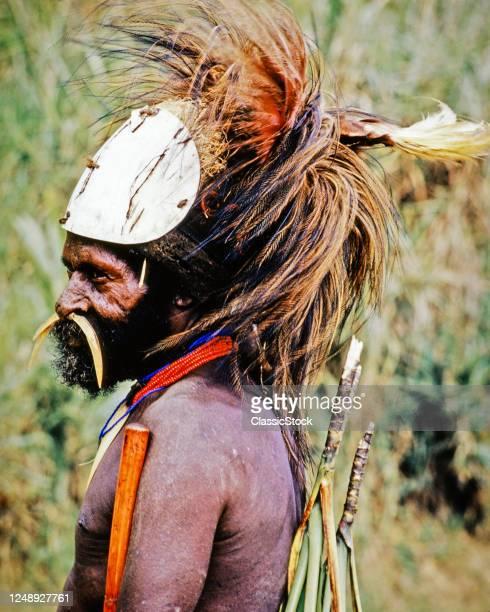 1960s Native Tribal Man Wearing Elaborate Headdress With Feathers Beads Necklace Bone In Nose Goroka Papua New Guinea