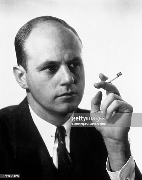 1960s PORTRAIT OF MAN SMOKING HOLDING A CIGARETTE