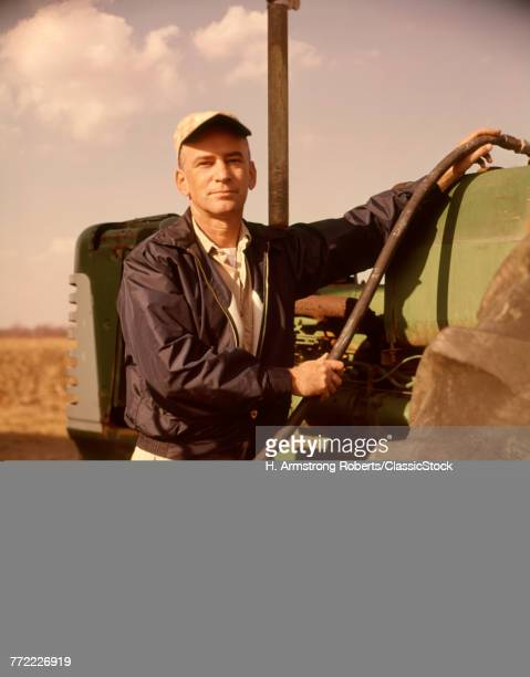 1960s PORTRAIT OF SERIOUS MAN FARMER LOOKING AT CAMERA FUEL INTO TRACTOR