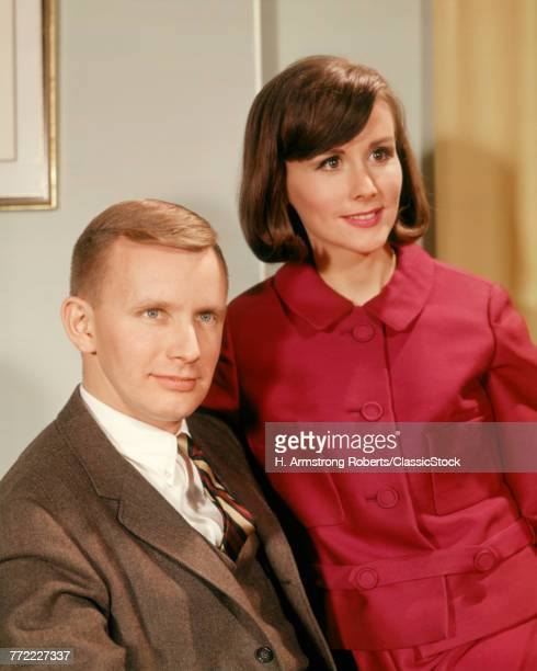 1960s PORTRAIT SERIOUS YOUNG COUPLE MAN IN BUSINESS SUIT WOMAN WEARING RED DRESS