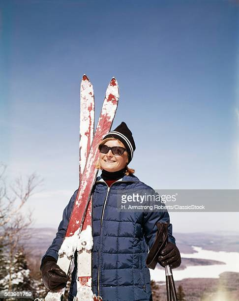 1960s PORTRAIT SMILING WOMAN OUTDOORS WEARING QUILTED DOWN JACKET SUNGLASSES HOLDING SKIS