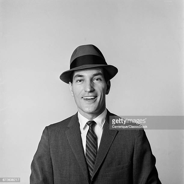 1960s PORTRAIT SMILING BUSINESSMAN WEARING HAT BUSINESS SUIT TIE LOOKING AT CAMERA