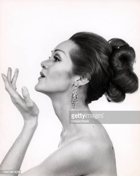 1960s PROFILE PORTRAIT OF ELEGANT GLAMOROUS WOMAN WITH BARE SHOULDERS AND HIGH FASHION MAKEUP AND HAIRSTYLE
