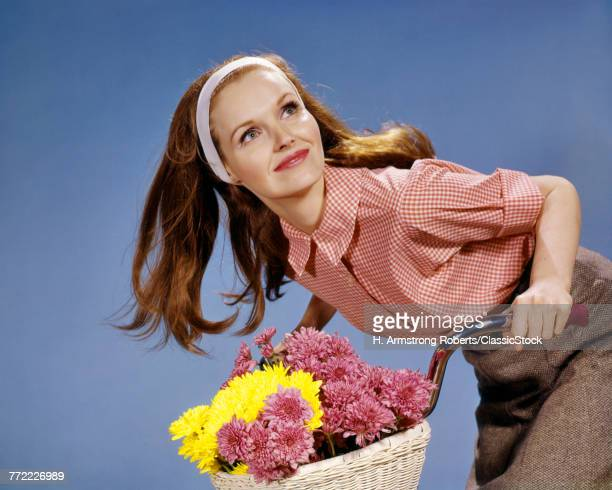 1960s REDHEAD WOMAN RIDING BICYCLE WITH BASKET FULL OF AUTUMN FLOWERS