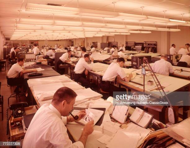 1960s ROOM FULL OF MANY MEN DESIGNERS WHITE COLLAR ARCHITECTS ENGINEERS SEATED AT DRAFTING TABLES WORKING