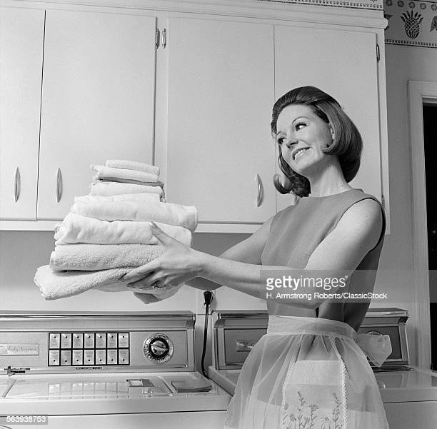 1960s SATISFIED WOMAN HOMEMAKER HOLDING FOLDED LAUNDRY