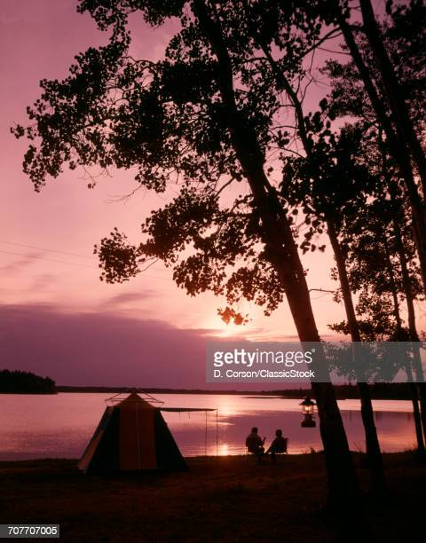 1960s SILHOUETTE OF ANONYMOUS COUPLE CAMPING BY LAKE AT SUNSET