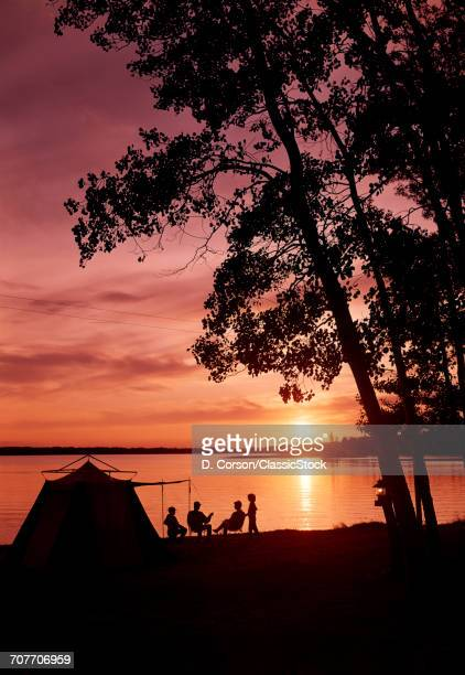 1960s SILHOUETTE OF ANONYMOUS FAMILY CAMPING BY LAKE AT SUNSET